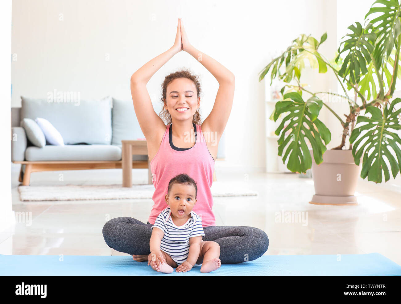 African-American woman with cute little baby practicing yoga at home - Stock Image