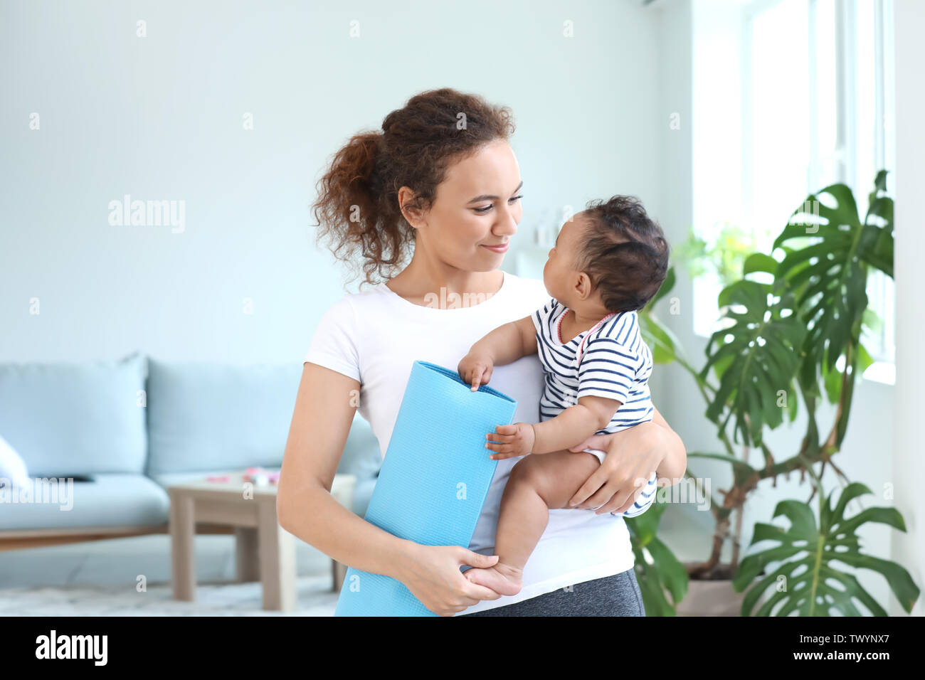 Sporty African-American woman with cute little baby at home - Stock Image