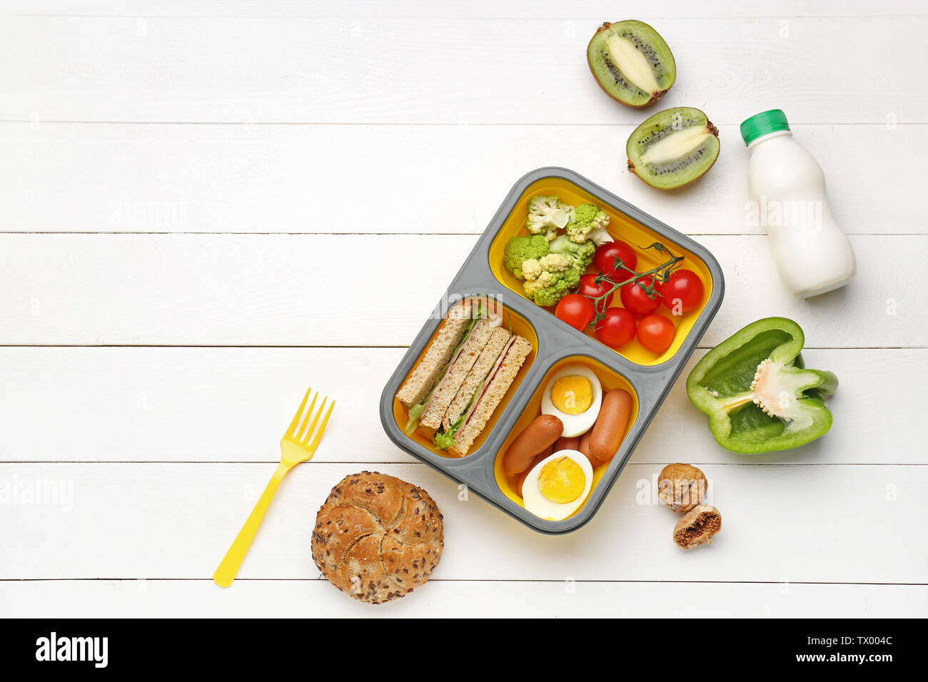 Lunch box with tasty food on white wooden background - Stock Image