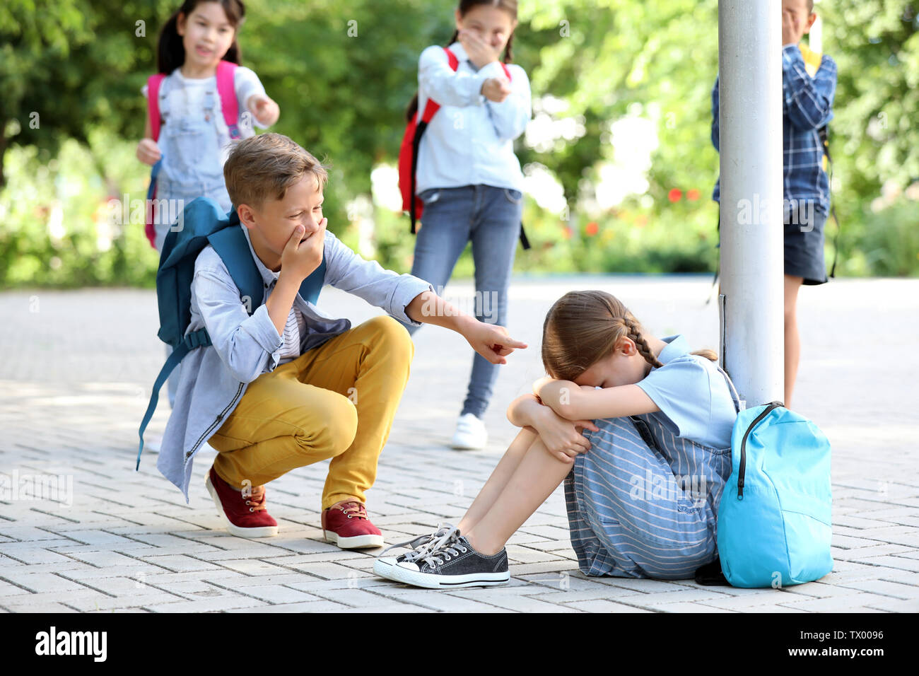 Bullied little girl with aggressive schoolmates outdoors - Stock Image