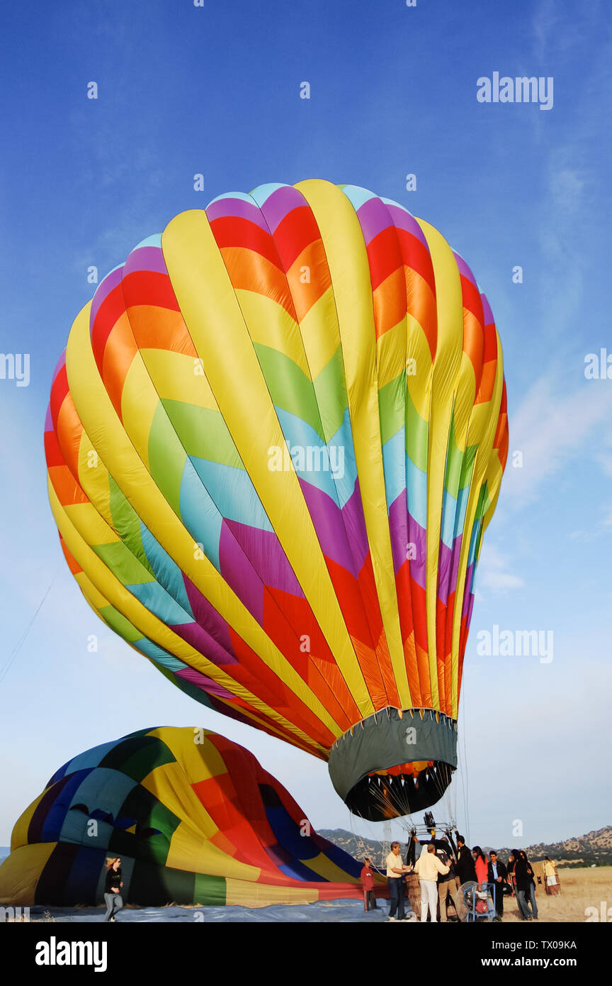 Passengers load into a coloful hot air baloon as the crew readies it for takeoff in Napa Valley, California, USA. Stock Photo