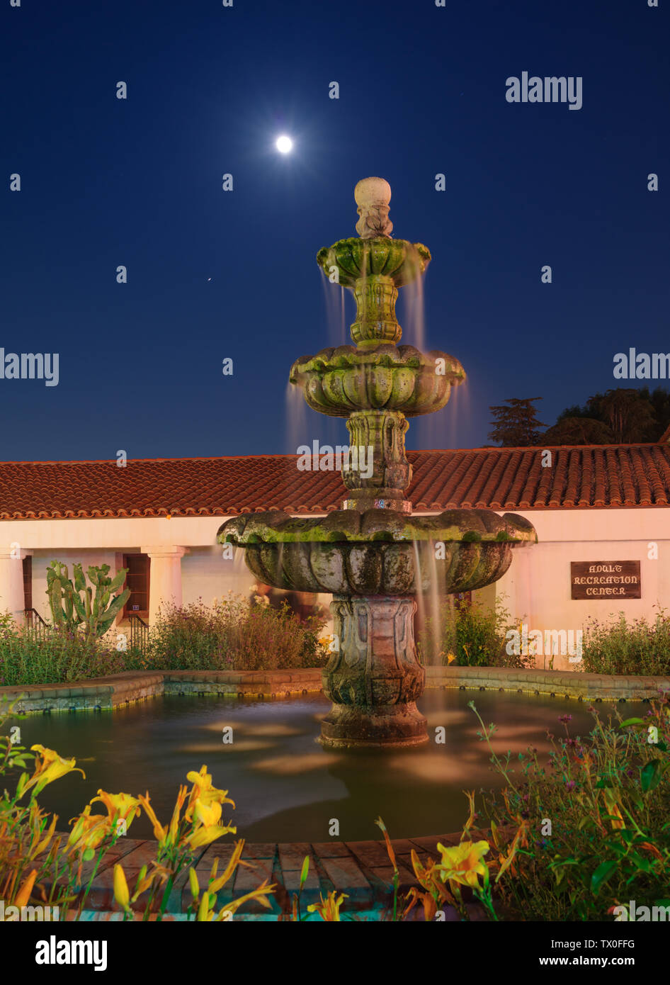 Image showing the rising full moon overt the Constitution Fountain at San Gabriel Mission Playhouse in California. - Stock Image