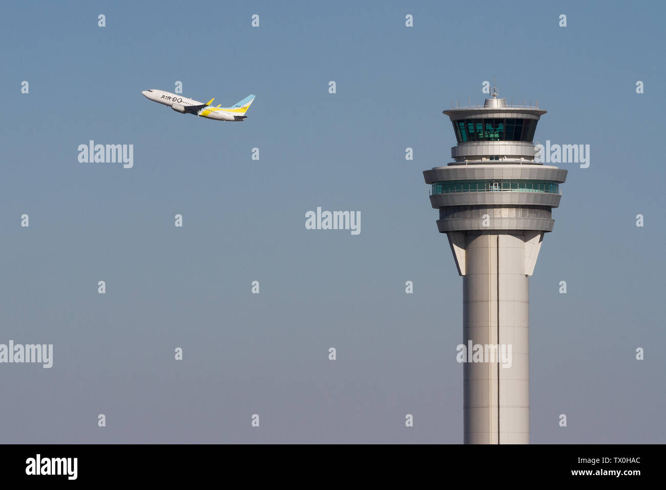 A boeing 737-700 with regional airline, Air Do trakes off behind the control tower at Haneda International Airport, Tokyo, Japan. Friday February 1st Stock Photo