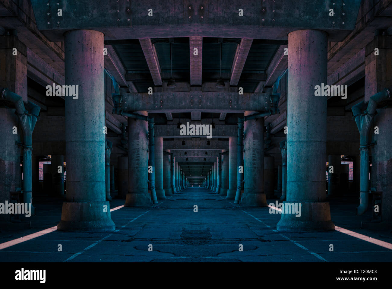A long passageway with tall, thick columns with an eerie pink and blue color tone - Stock Image