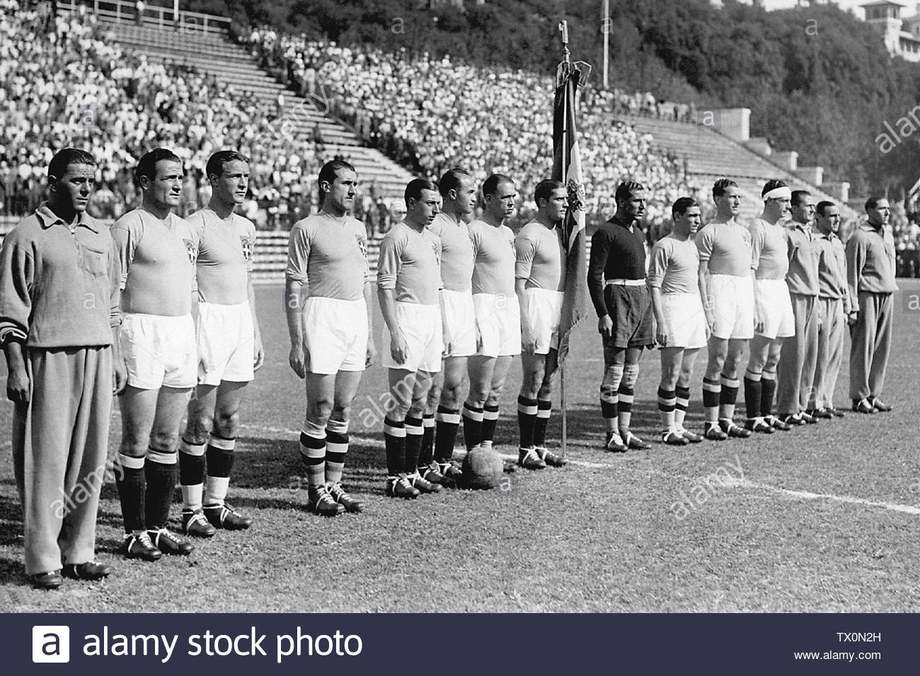 'Italian national soccer team players pose for a group picture, 10 June 1934 in Rome, before their World Cup final against Czechoslovakia. Italy won the title beating Czechoslovakia 2-1 in extra time. (From 2nd L : Luis Monti, Eraldo Monzeglio, Angelo Schiavio, Raimundo Orsi, Giovanni Ferrari, Enrique Guaita, Giuseppe Meazza - with flag -, Giampiero Combi, Attilio Ferraris IV, Luigi Allemandi, Luigi Bertolini); 10 June 1934, 17:14; Gazzetta dello Sport; STAFF/AFP/Getty Images; ' - Stock Image