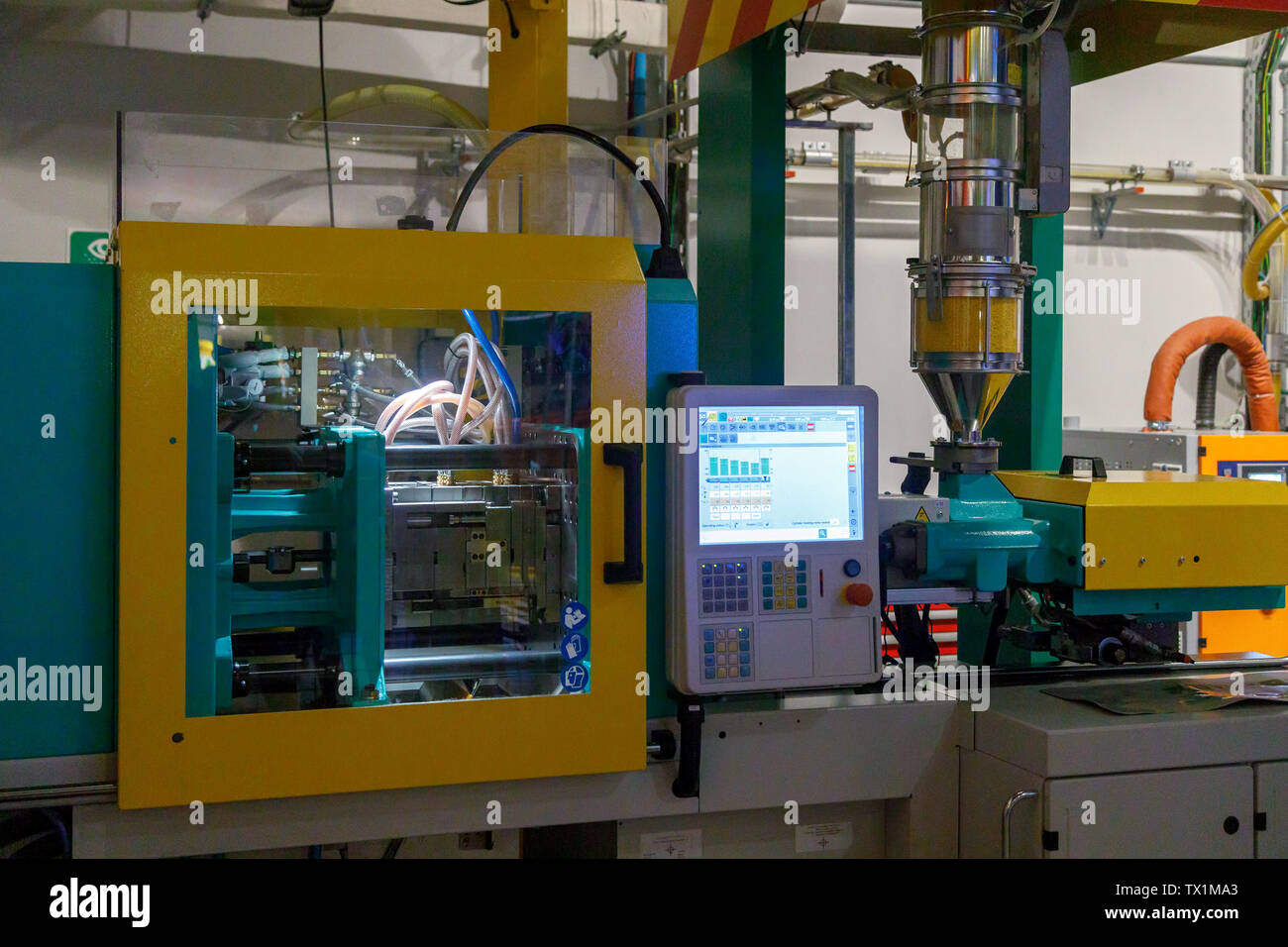DUBAI, UAE, JANUARY 09, 2019: Plastic injection molding machine in the process of creating a brick Lego in Legoland - Stock Image