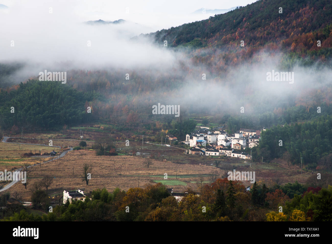An ancient village shrouded by clouds and fog. Stock Photo