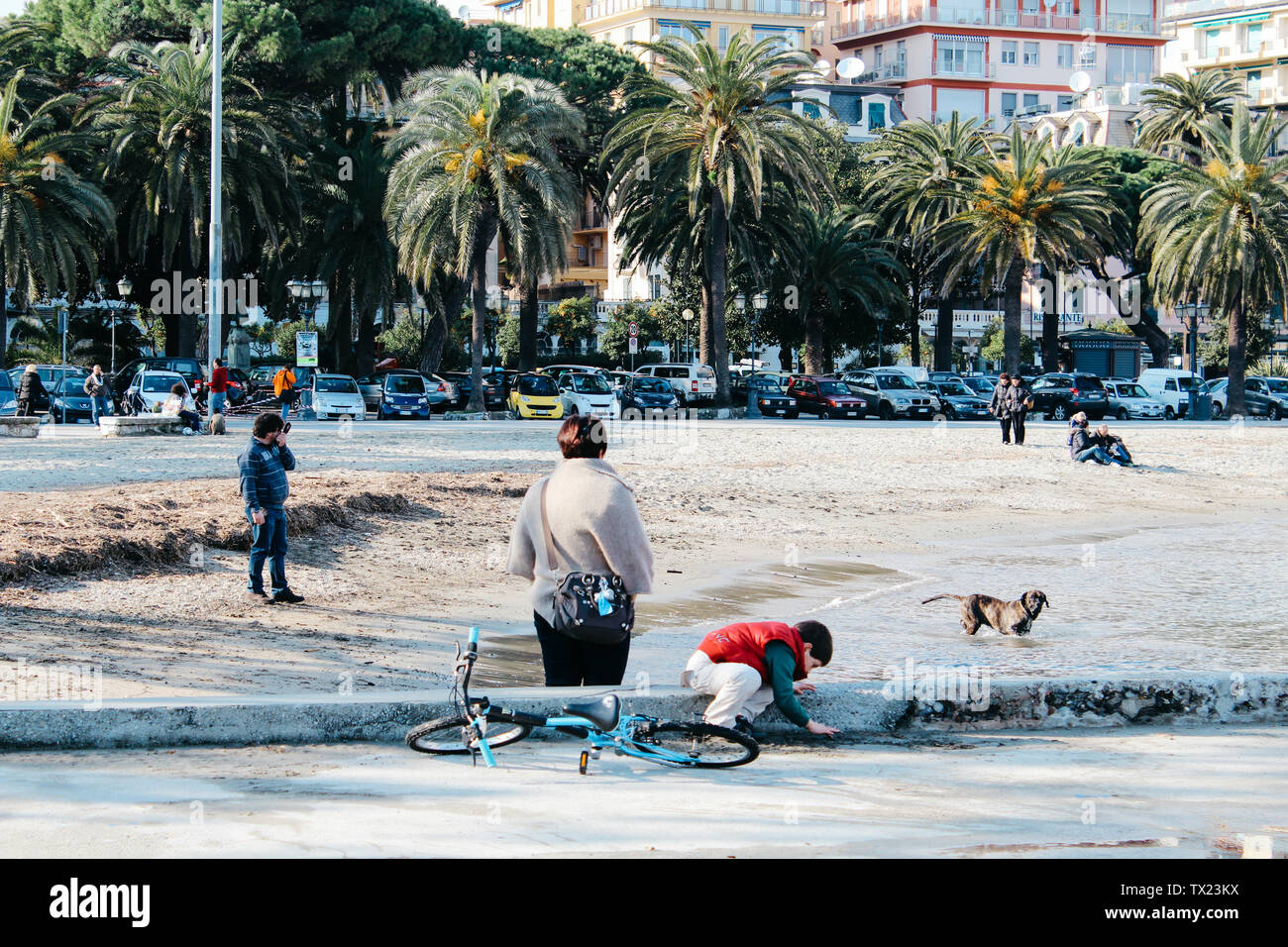 Rapallo, Italy - 03 27 2013: People on the beach. View of the streets of Rapallo - Stock Image