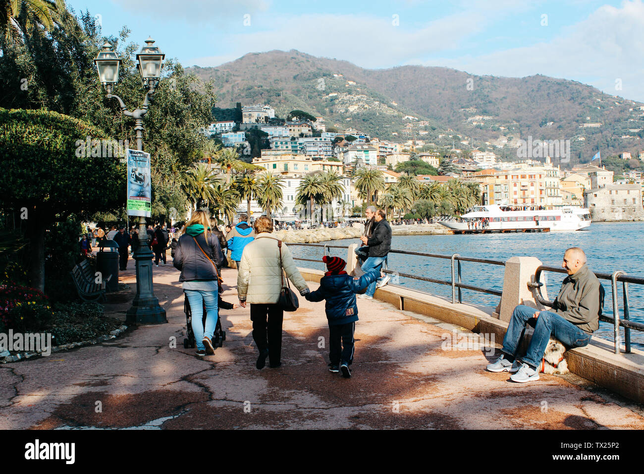 Rapallo, Italy - 03 27 2013: people walk along the waterfront. View of the streets of Rapallo. - Stock Image