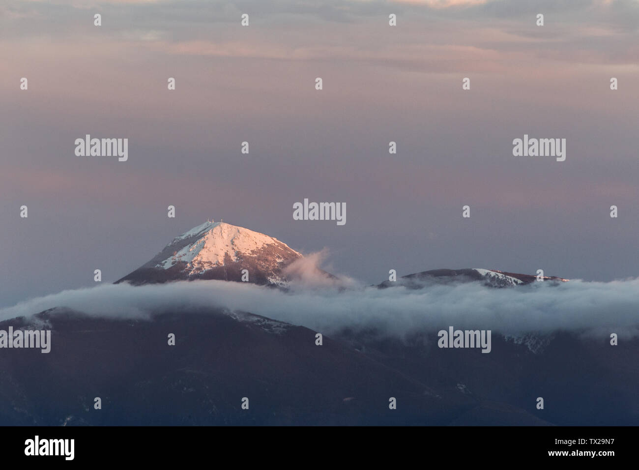 Mountain top covered by snow in the middle of clouds - Stock Image