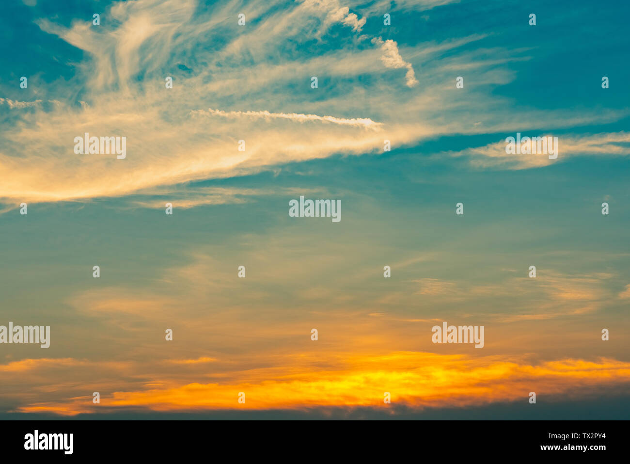 Beautiful blue and golden sky and clouds abstract background. Yellow-orange clouds on sunset sky. Warm weather background. Art picture of sky at sunse - Stock Image