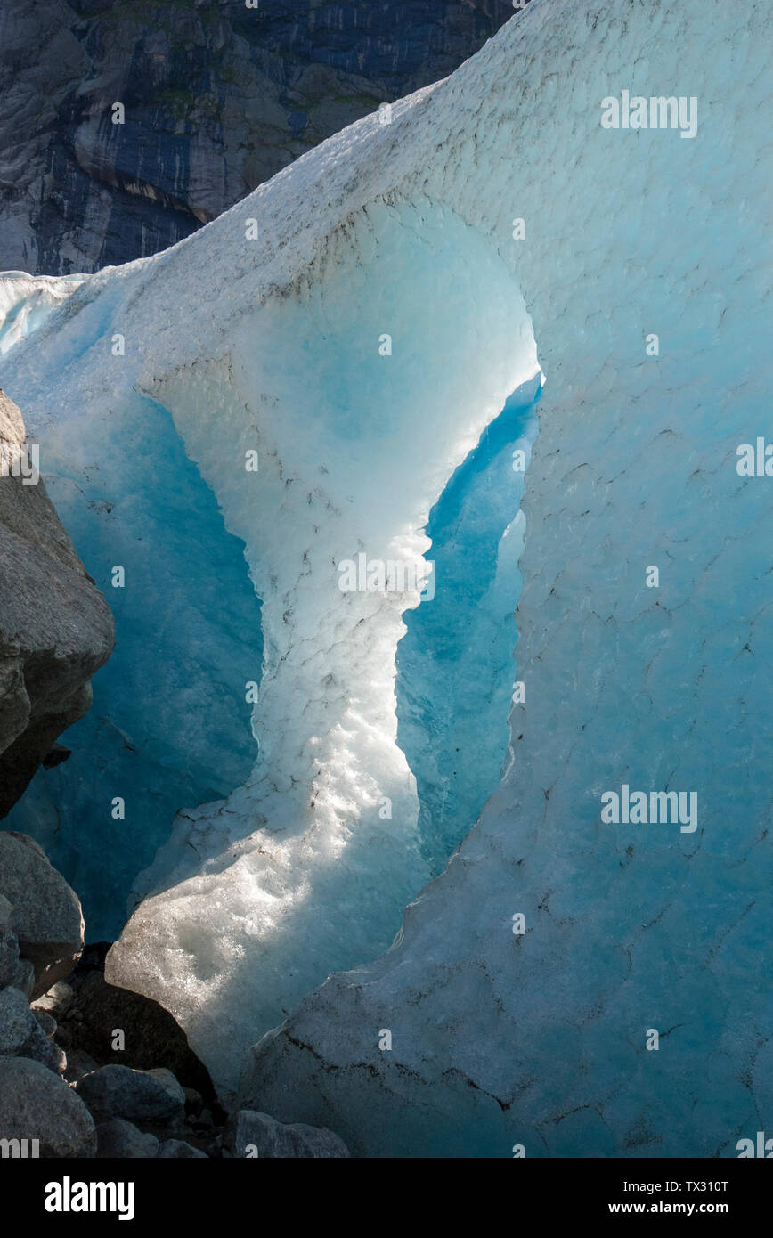 A big hole in a glacier with melting ice and falling water drops, Briksdal Glacier, Norway Stock Photo
