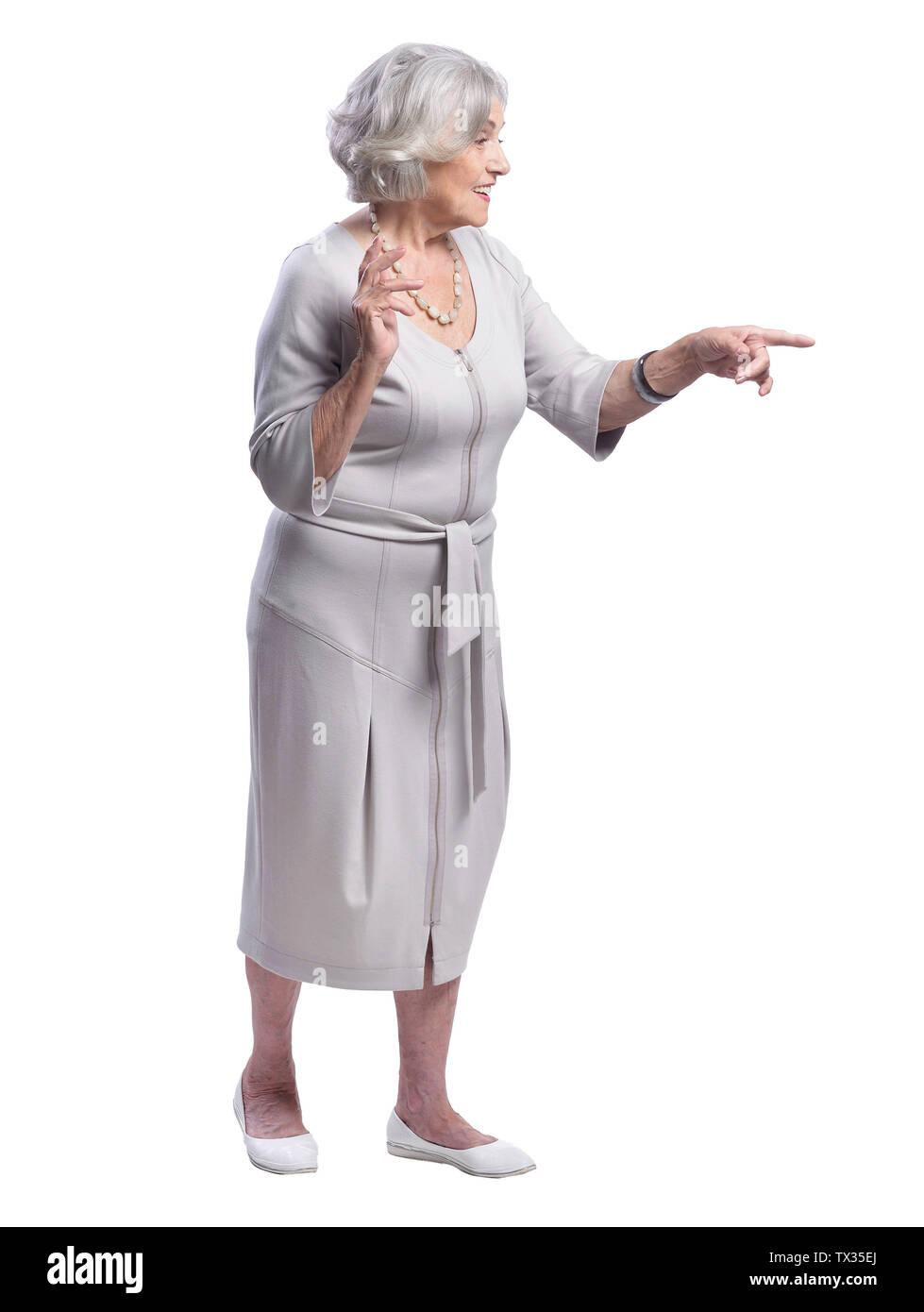Smiling senior woman pointing isolated on white background - Stock Image