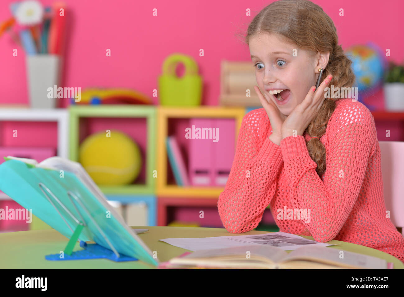 Cute schoolgirl doing homework at her room at home - Stock Image