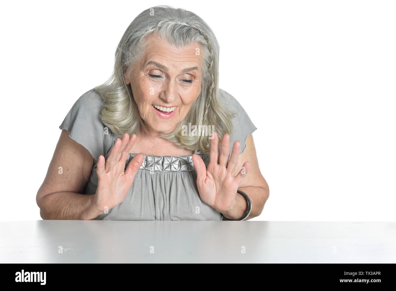 Emotional senior woman at table isolated on white background - Stock Image
