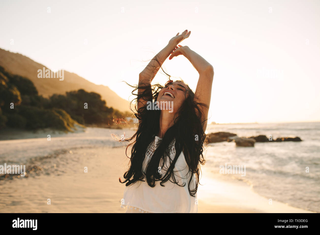 Beautiful woman enjoying a summer day on the beach. Caucasian female having a great time on her vacation. - Stock Image