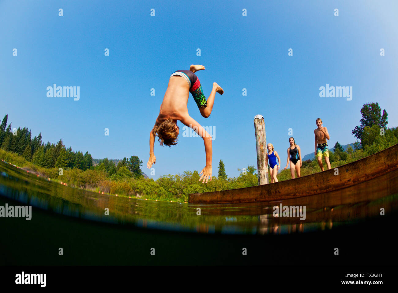 Boy somersaulting off dock into sunny summer lake Stock Photo