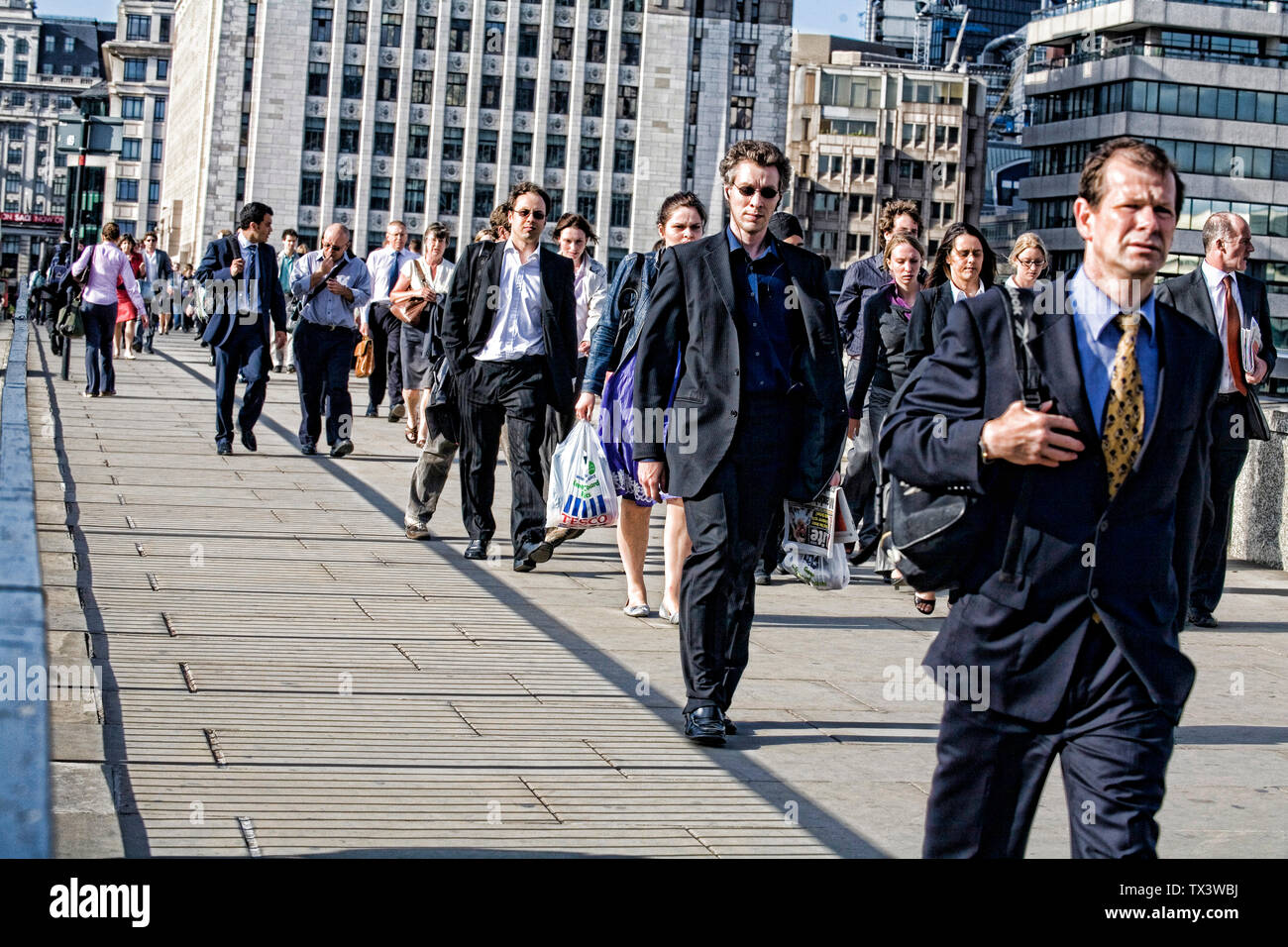 People crossing London bridge at rush hours London England Britain UK - Stock Image