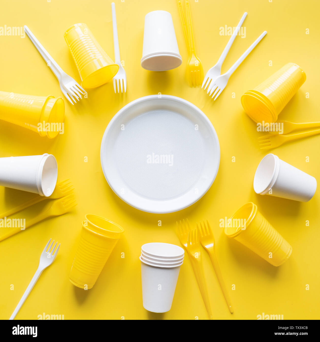 Disposable picnic utensils for recycling on yellow. Environment