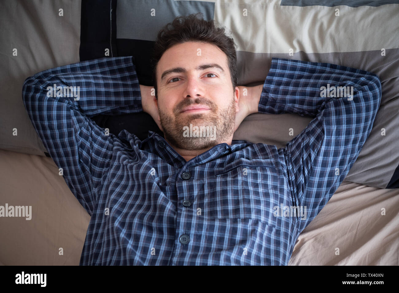 Relaxed man lying in bed and feeling good - Stock Image