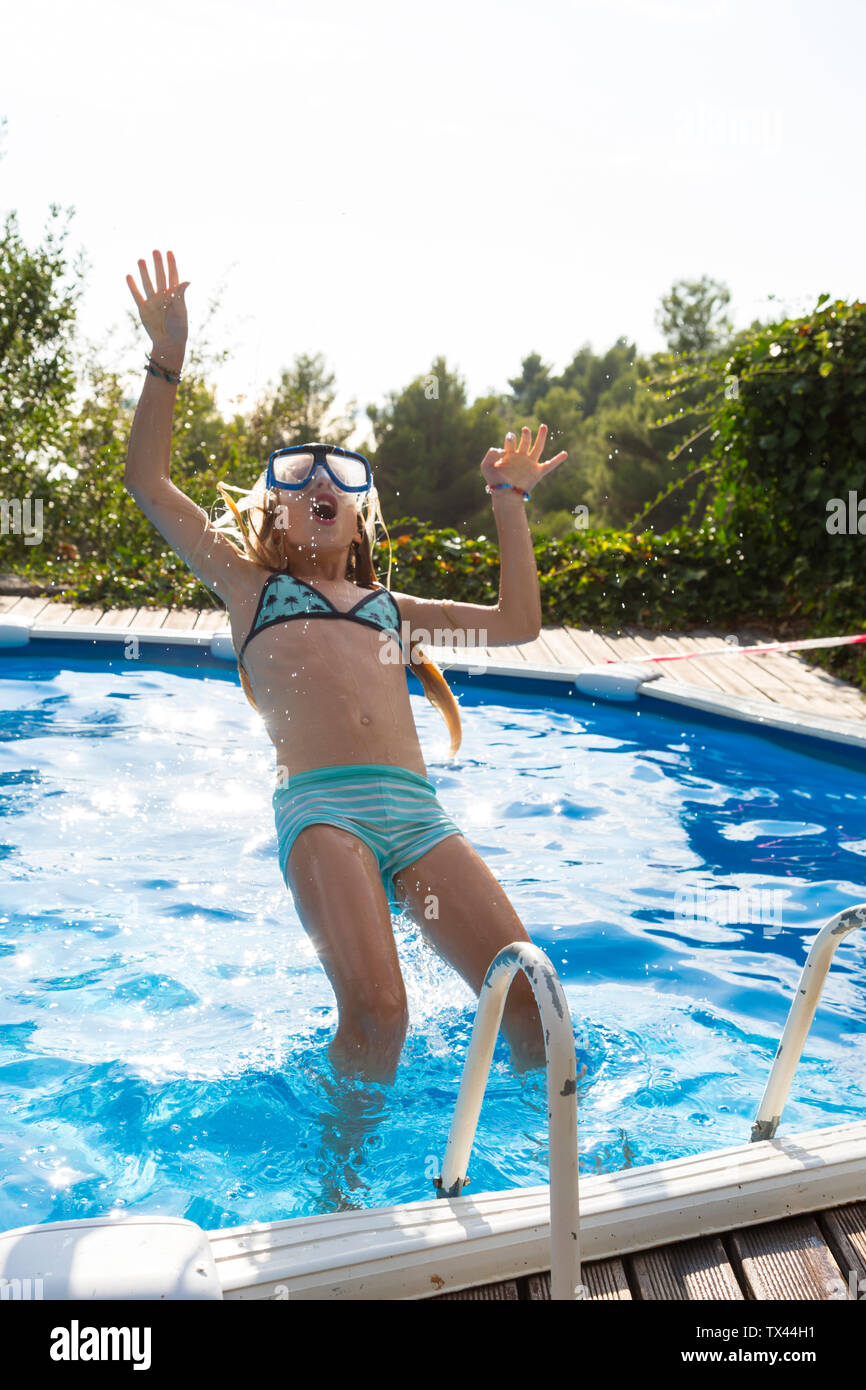 Girl jumping into swimming pool - Stock Image