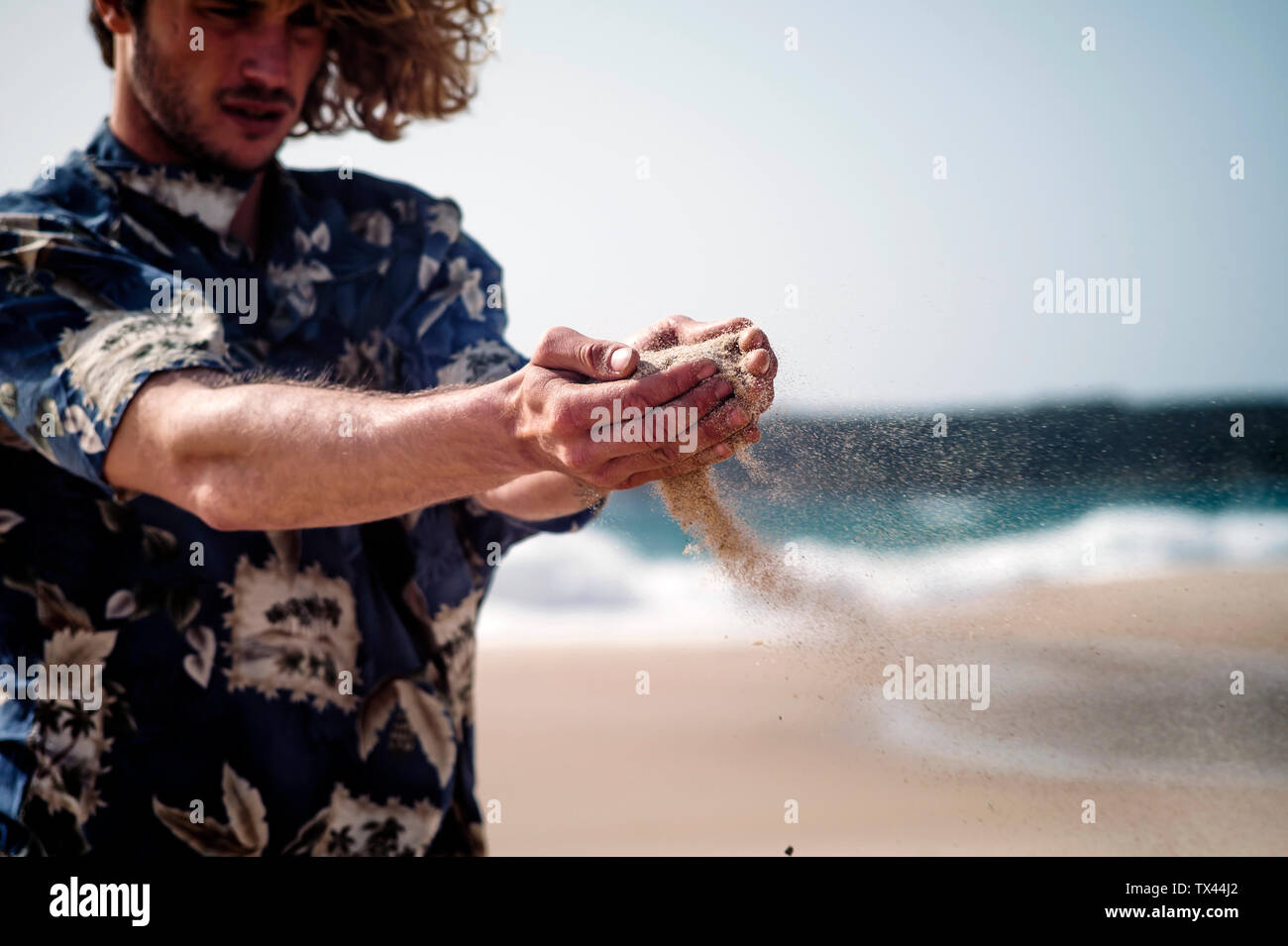 Man on the beach trickling sand through his hands - Stock Image