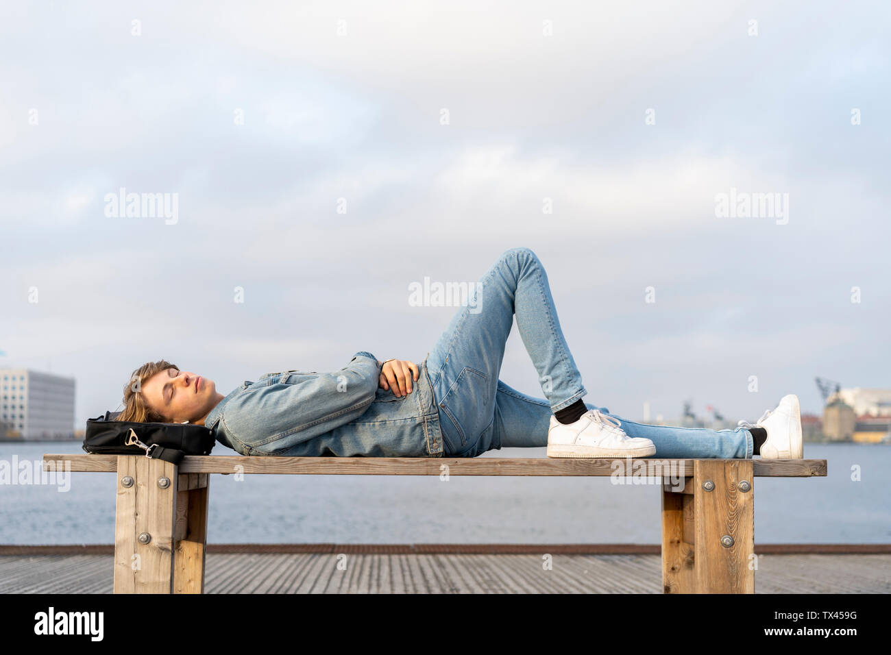 Denmark, Copenhagen, young man lying on a bench at the waterfront - Stock Image