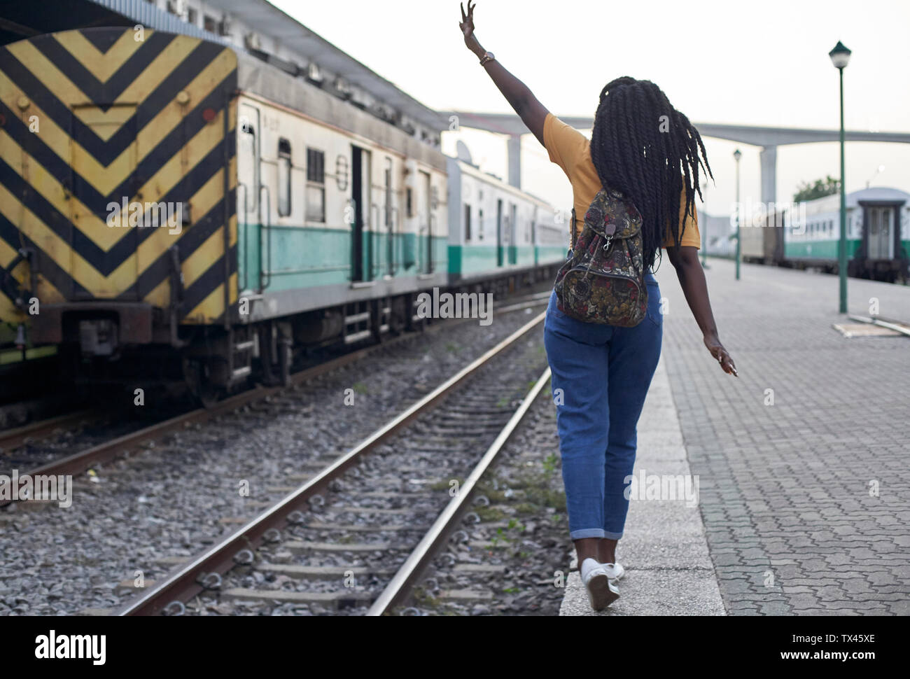 Rear view of young woman at the edge of the rail at the train station Stock Photo