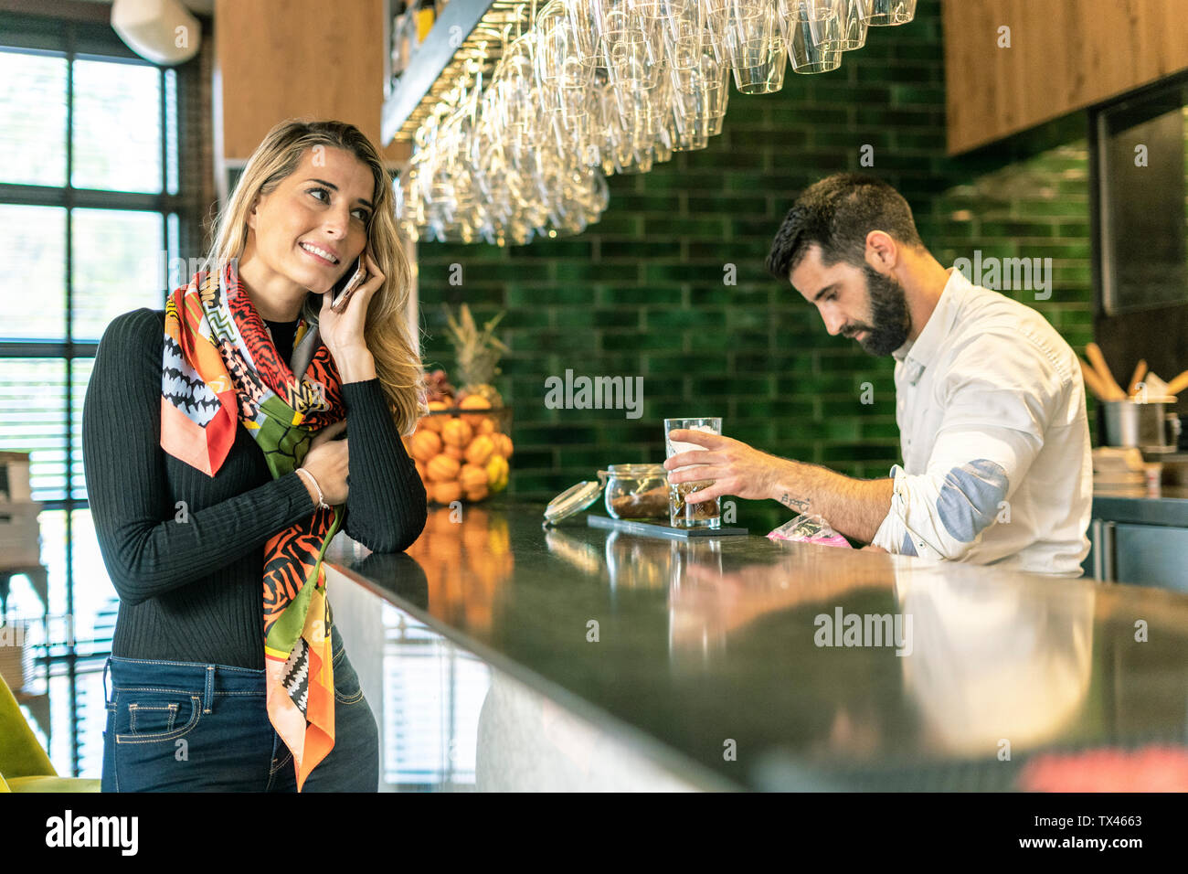 Smiling woman on cell phone at the counter of a bar with barkeeper preparing a cocktail - Stock Image