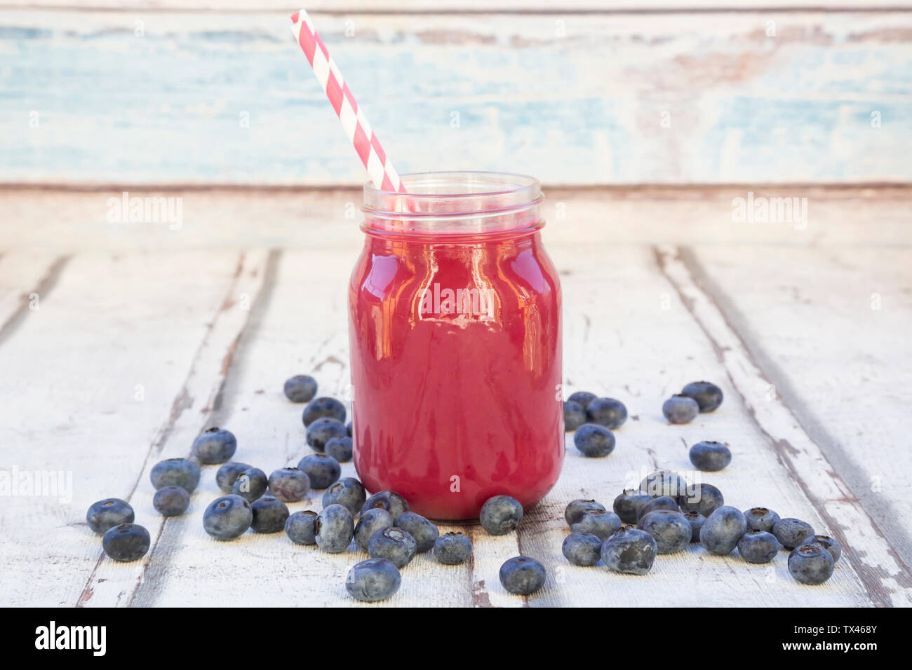 Blueberry smoothie in glass with drinking straws - Stock Image
