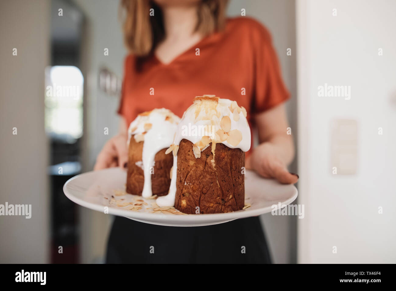 Woman serving garnished cake on plate Stock Photo