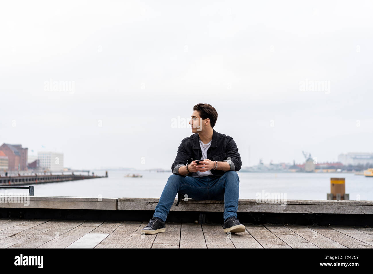 Denmark, Copenhagen, young man sitting at the waterfront with cell phone - Stock Image