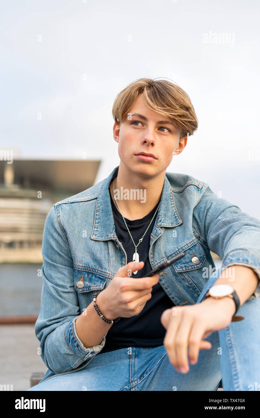 Denmark, Copenhagen, young man at the waterfront using cell phone - Stock Image