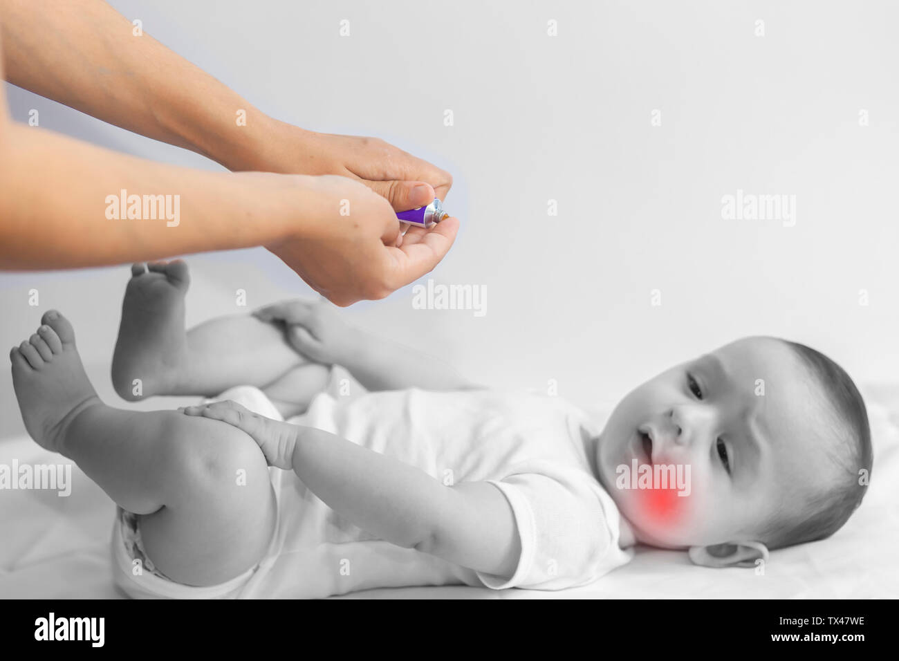 Baby boy teething pain. Little 6-month baby having teeth pains. Mother rubbing gel to her little baby boy's teeth. Medicine and health concept. - Stock Image