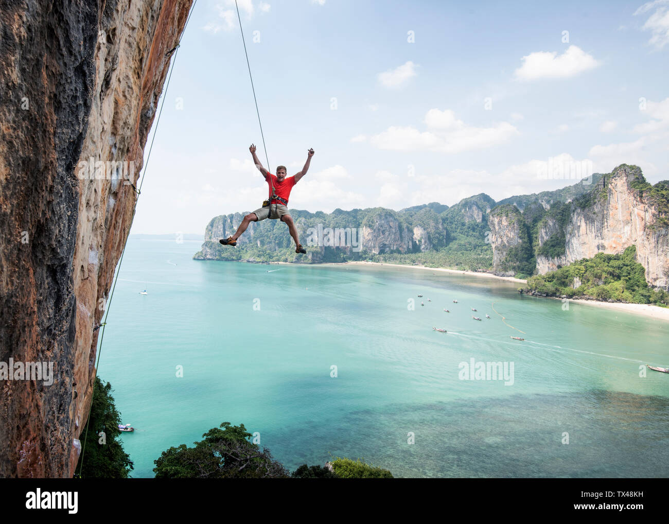 Thailand, Krabi, Thaiwand wall, climber abseiling from rock wall above the sea Stock Photo