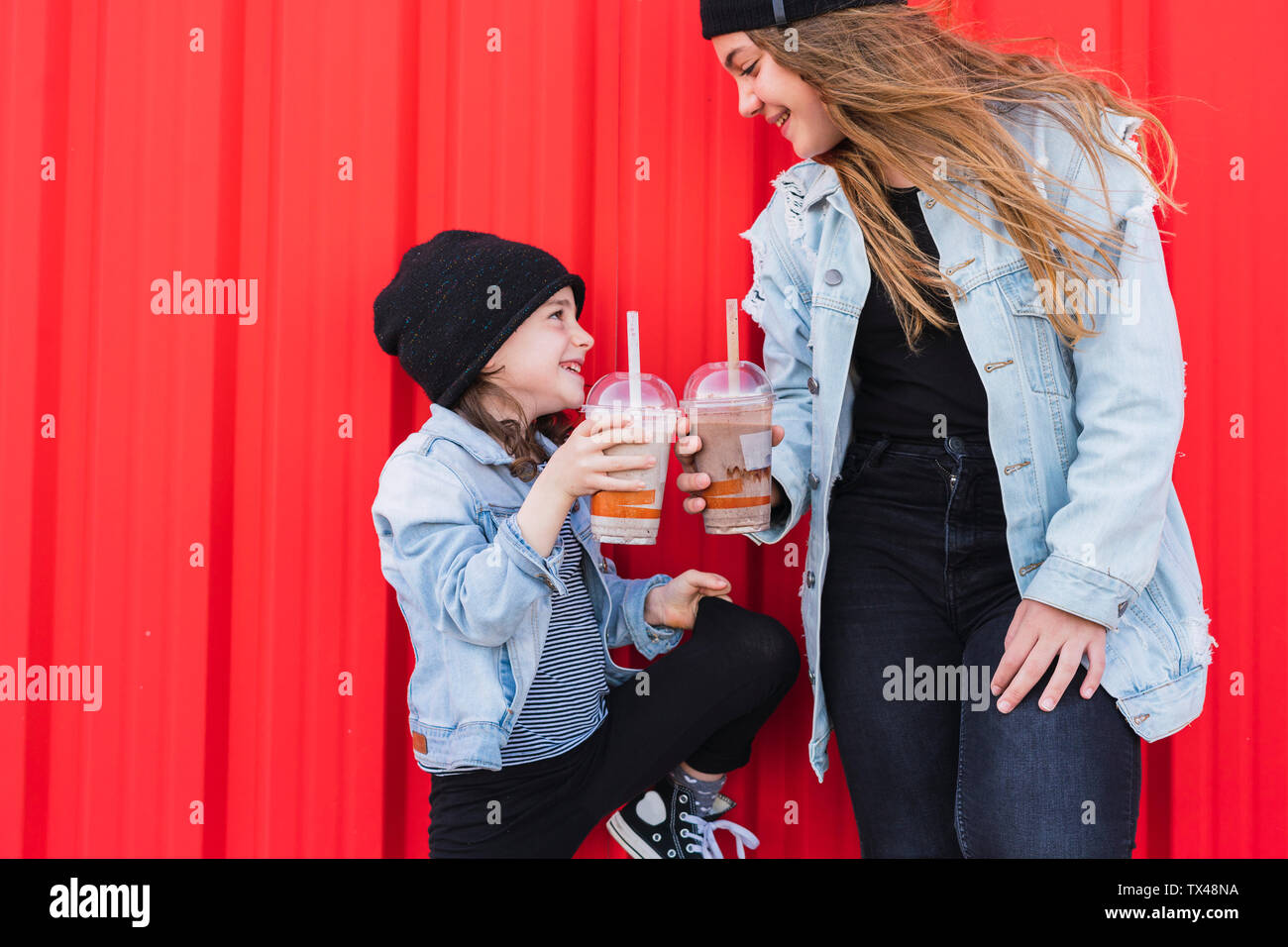 Teenage girl and little sister toasting with drinks Stock Photo