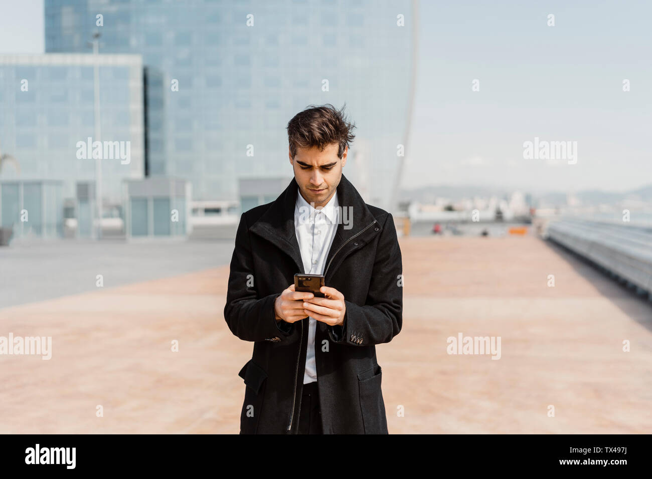 Businessman using cell phone in the city - Stock Image