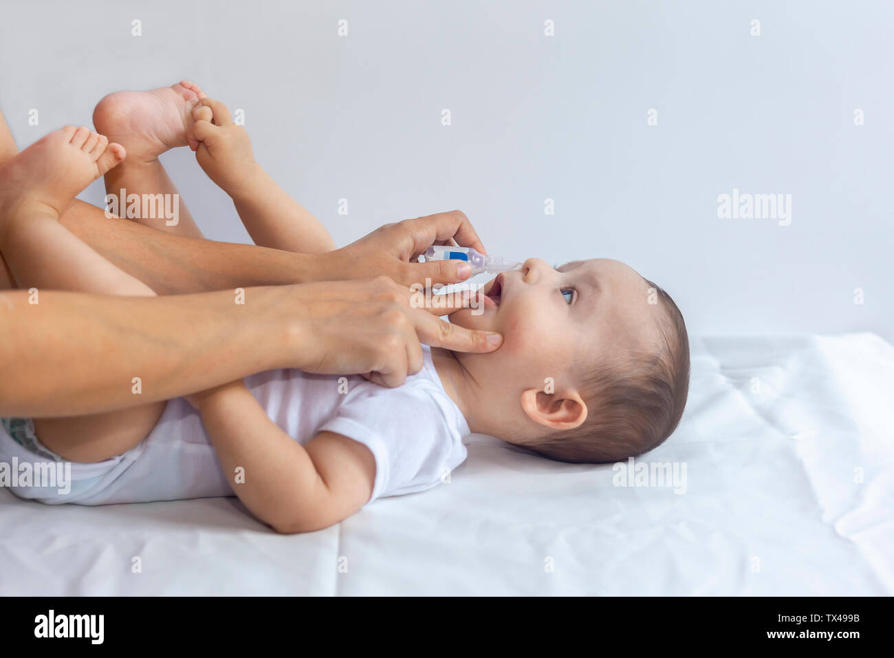 Mother put saline drops in infant's nose. Little boy getting nasal drops. 6-month baby boy gets nose drops. Pediatrician putting saline drops in infan Stock Photo