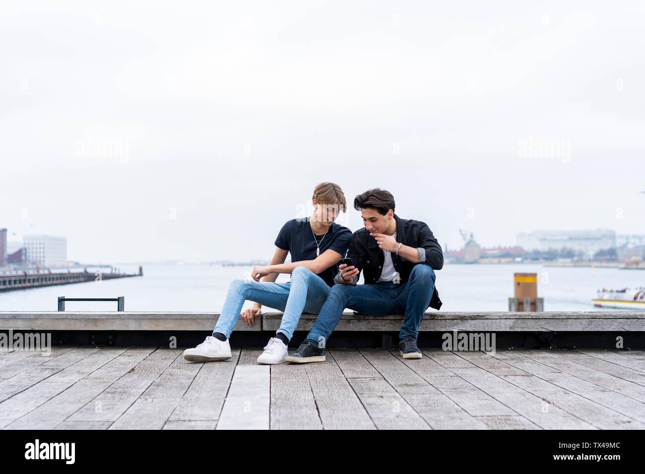 Denmark, Copenhagen, two young men sitting at the waterfront using cell phone - Stock Image
