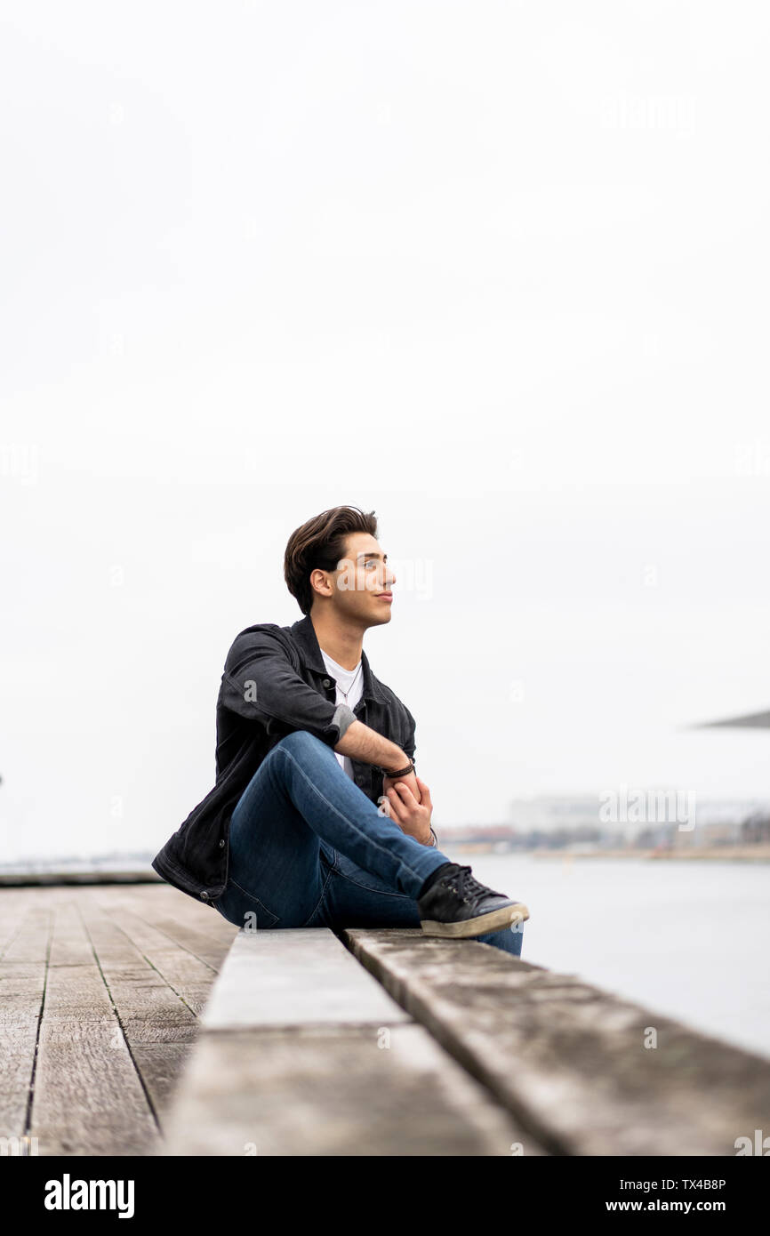 Denmark, Copenhagen, young man sitting at the waterfront - Stock Image