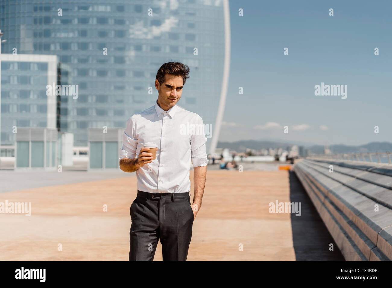 Portrait of businessman with takeaway coffee in the city - Stock Image