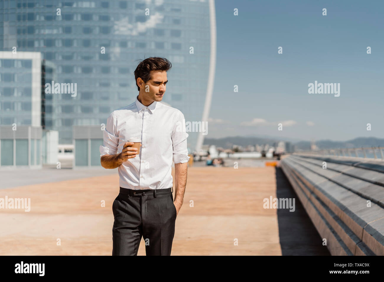 Businessman with takeaway coffee in the city - Stock Image