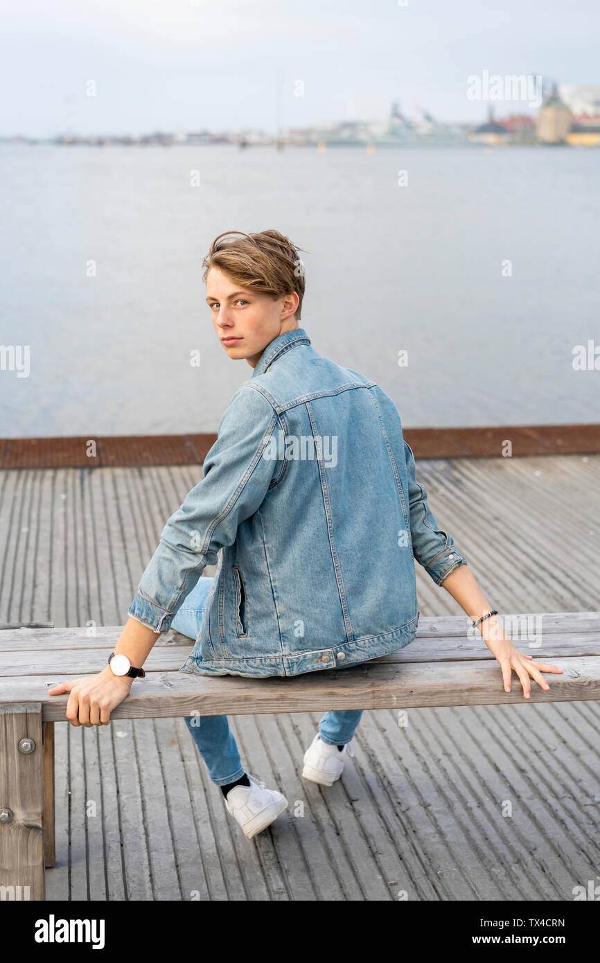 Denmark, Copenhagen, young man sitting on a bench at the waterfront - Stock Image