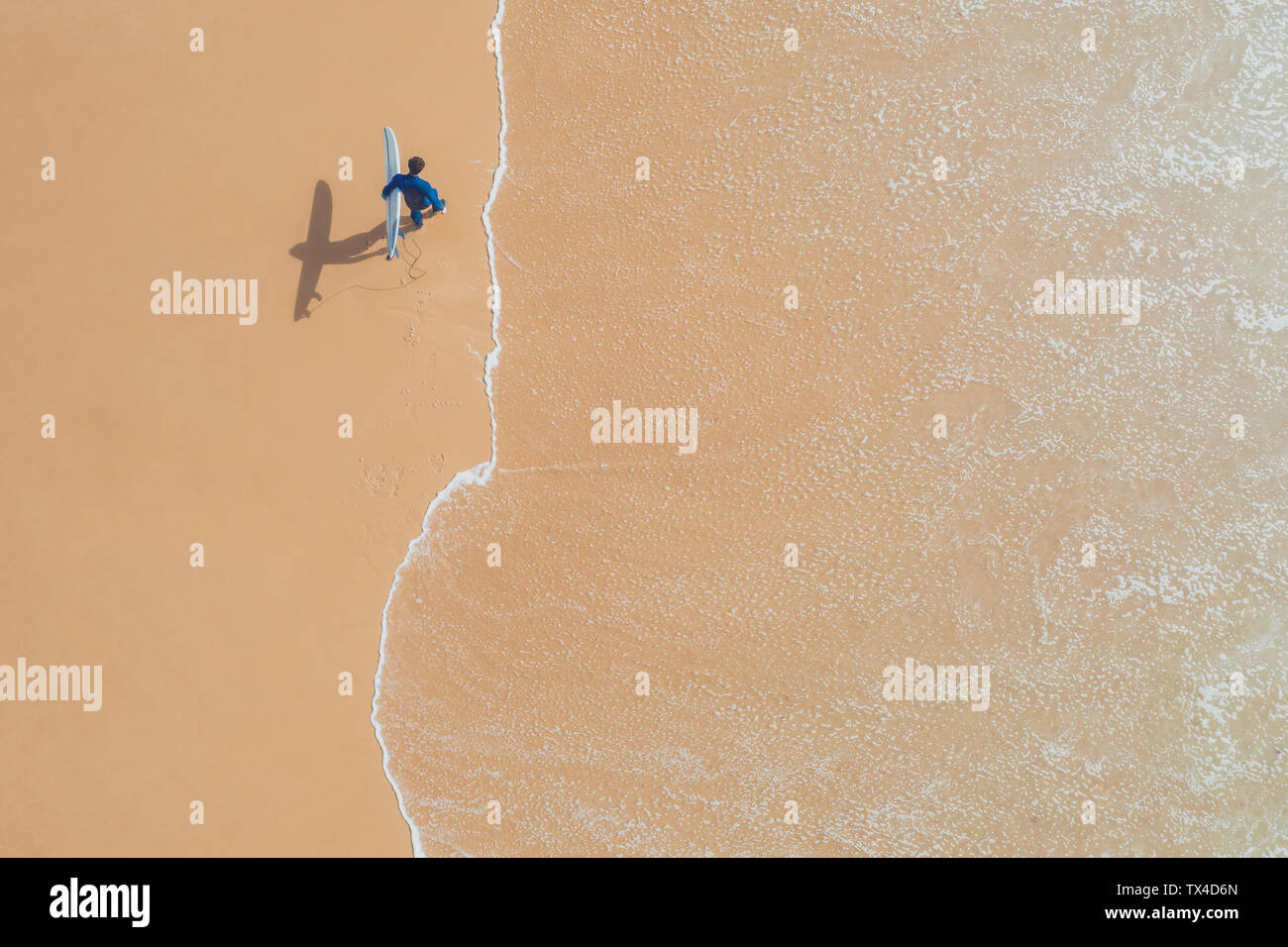 Portugal, Algarve, Sagres, Praia da Mareta, aerial view of man carrying surfboard on the beach Stock Photo