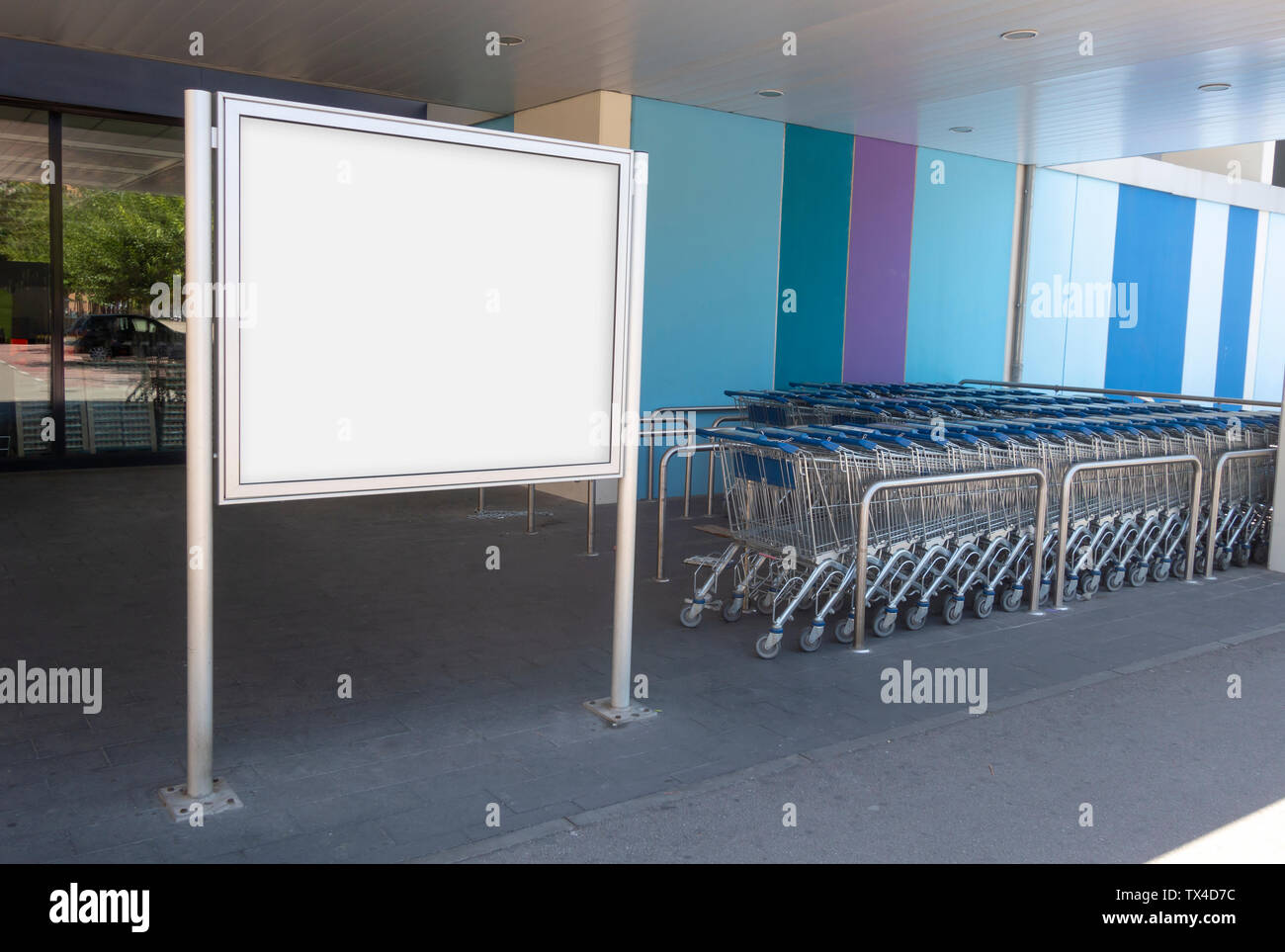 Blank billboard mock up in a supermarket, in front of shopping carts Stock Photo