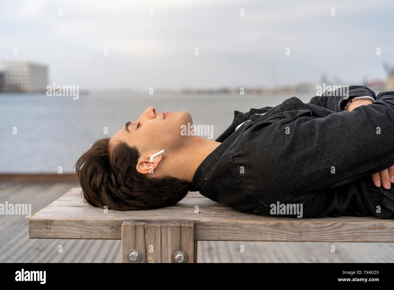 Denmark, Copenhagen, young man with earbuds lying on a bench at the waterfront - Stock Image