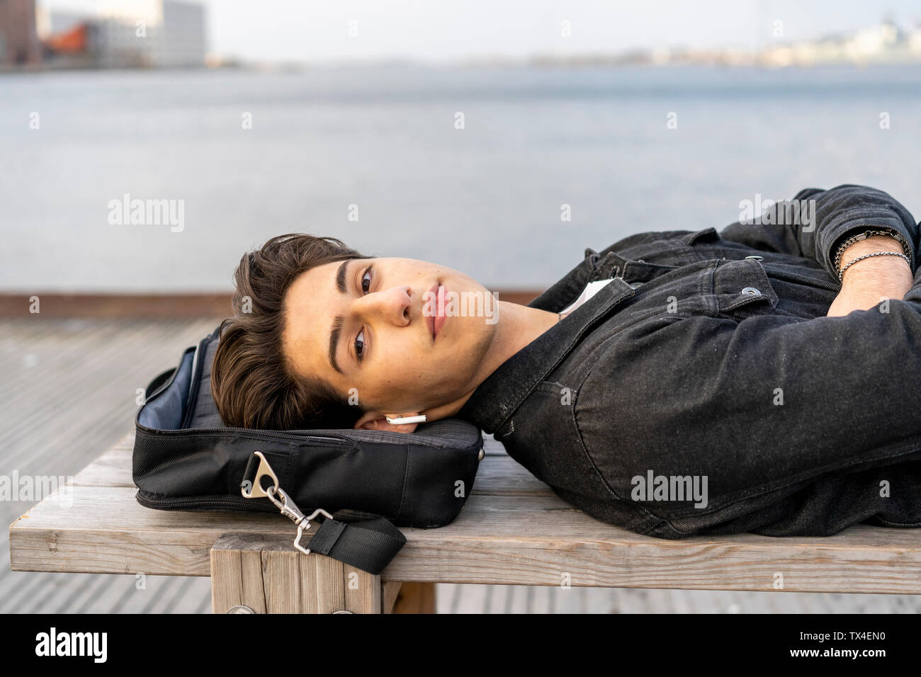 Denmark, Copenhagen, portrait of young man with earbuds lying on a bench at the waterfront - Stock Image