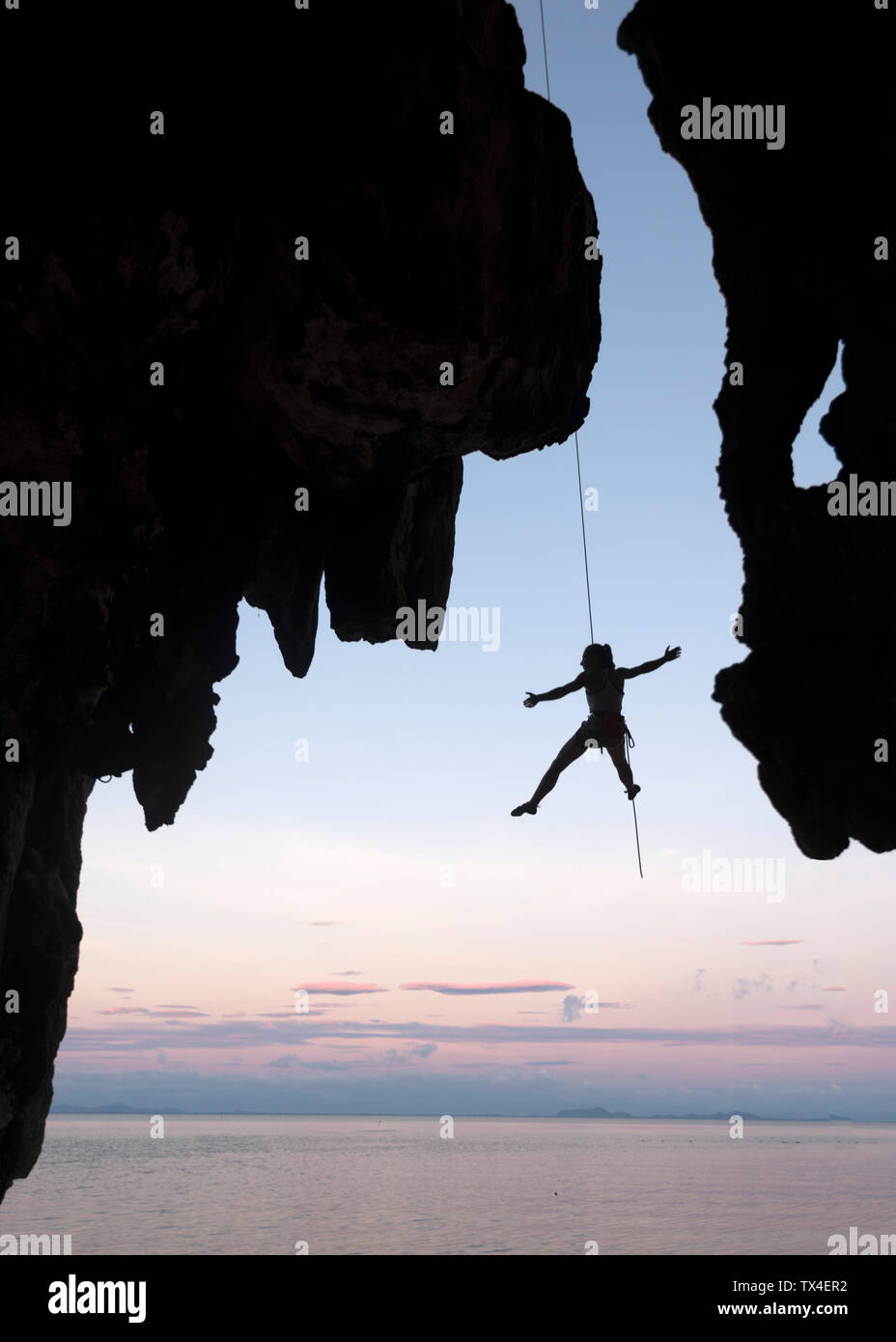 Thailand, Krabi, Lao Liang island, climber abseiling from rock wall above the sea Stock Photo