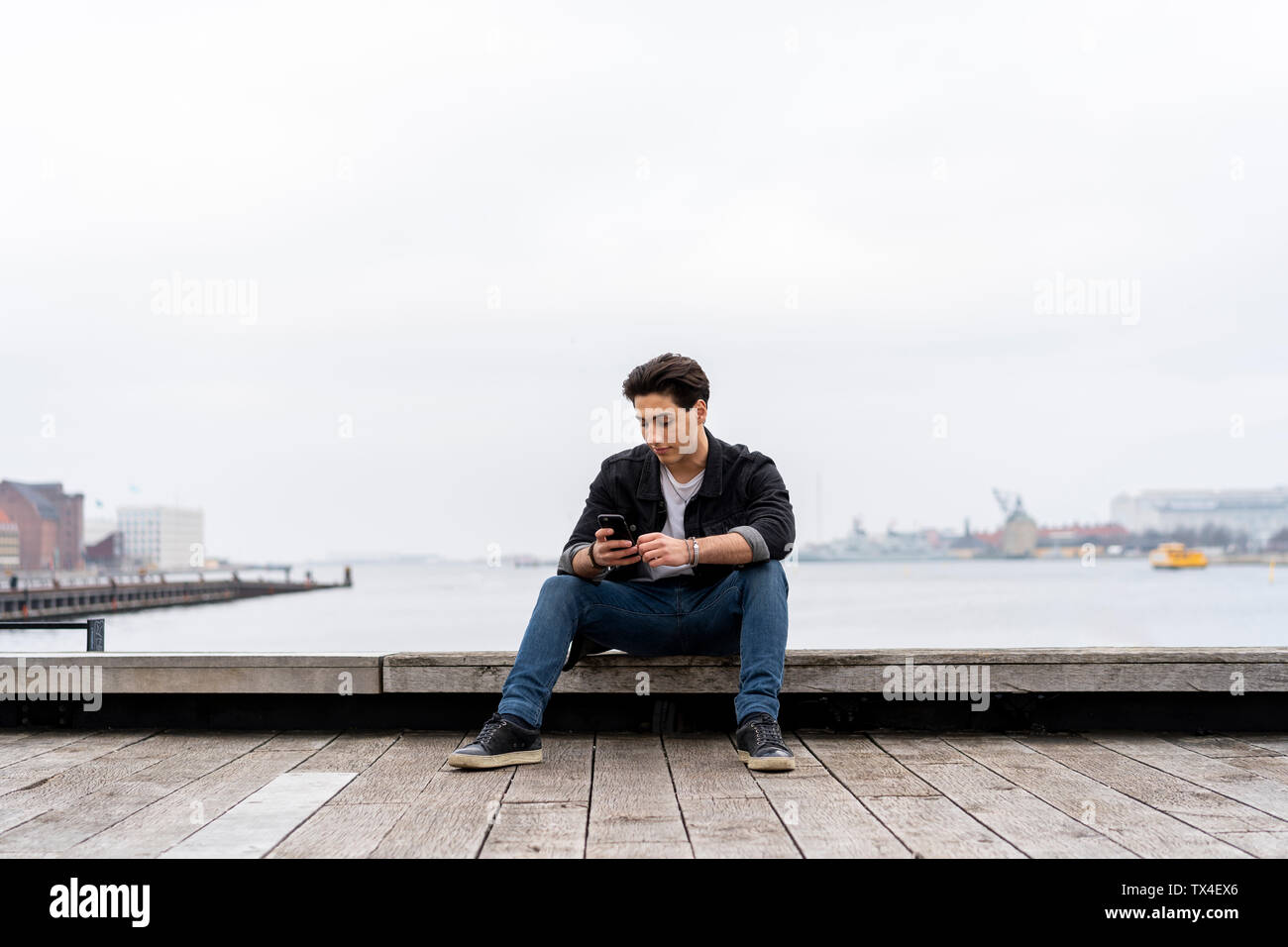 Denmark, Copenhagen, young man sitting at the waterfront using cell phone - Stock Image