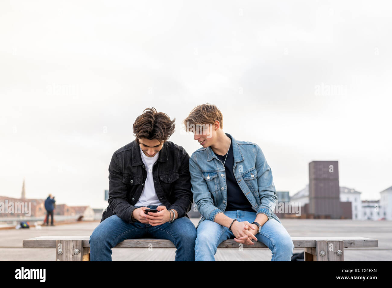 Denmark, Copenhagen, two young men sitting on a bench using cell phone - Stock Image